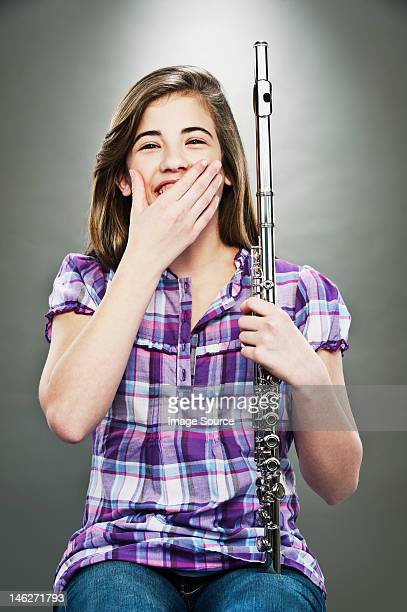 Portrait of young teenage girl laughing and holding flute