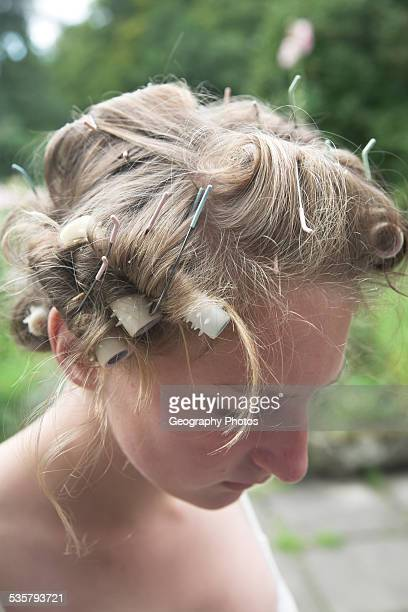 portrait of young teenage girl with curlers in her hair looking down thoughtfully