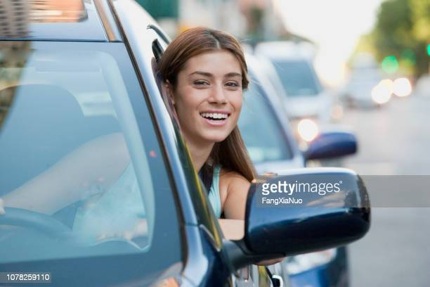 portrait of young teenage woman leaning out of car - car insurance stock pictures, royalty-free photos & images