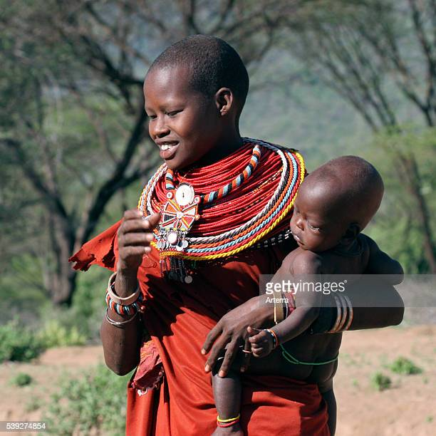 Portrait of young Turkana woman with baby in traditional red clothing in northwest Kenya East Africa