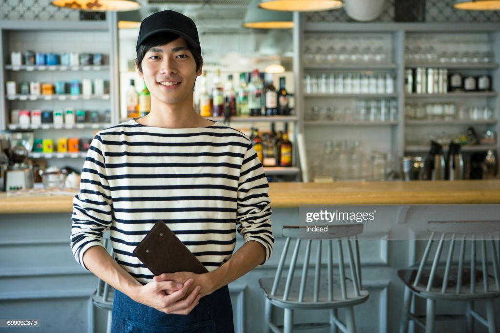 Portrait of young waiter in restaurant : ストックフォト