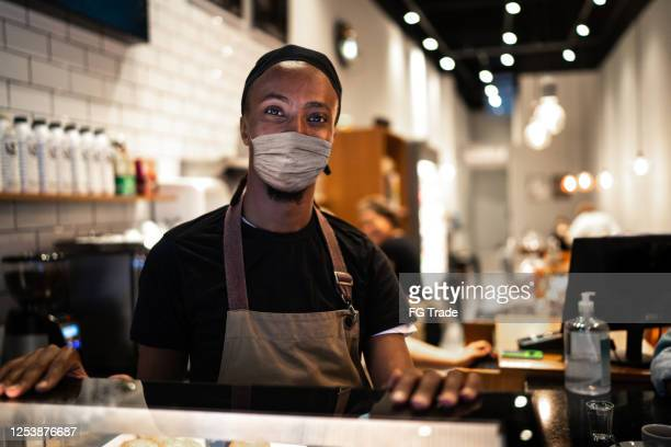 portrait of young waiter with face mask in coffee shop - reopening stock pictures, royalty-free photos & images