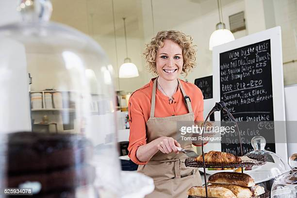 Portrait of young waitress holding plate with sweet buns