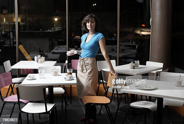 Portrait of young waitress in empty cafe, cleaning, night
