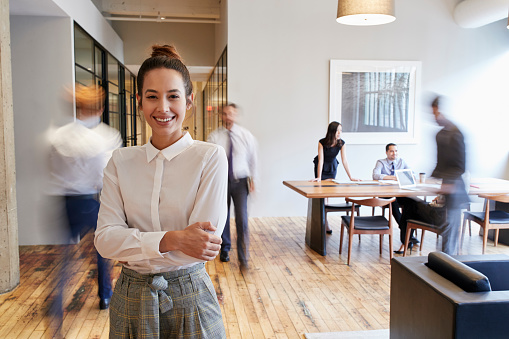 Portrait of young white woman in a busy modern workplace 904598344