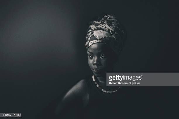 portrait of young woman against black background - nairobi stock pictures, royalty-free photos & images