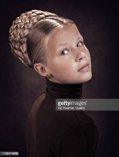 portrait of young woman against black background - val thoermer stock-fotos und bilder