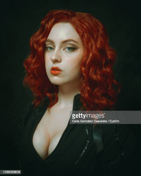 portrait of young woman against black background - dyed red hair stock pictures, royalty-free photos & images