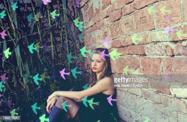 Portrait Of Young Woman Against Brick Wall