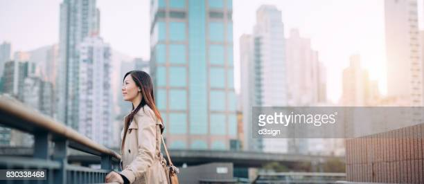 Portrait of young woman against commercial cityscape on a fresh morning
