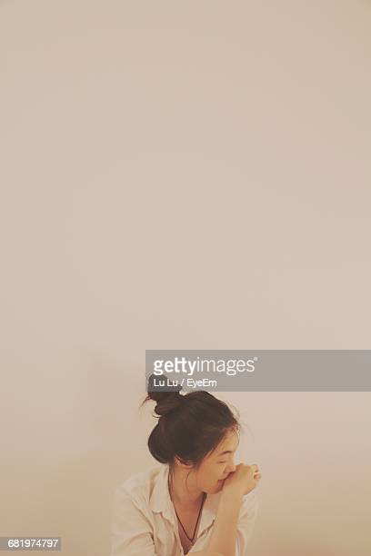 Portrait Of Young Woman Against Empty Wall