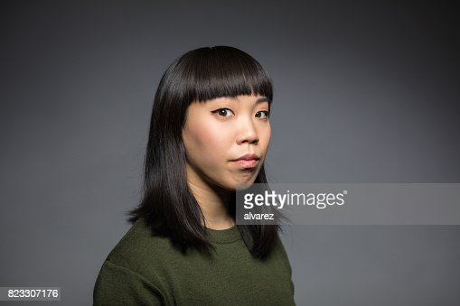 Portrait Of Young Woman Against Gray Background