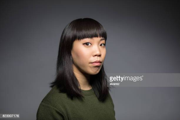 portrait of young woman against gray background - black hair stock pictures, royalty-free photos & images