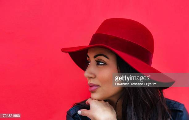 portrait of young woman against red background - red hat stock pictures, royalty-free photos & images