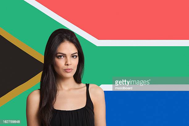portrait of young woman against south african flag - south african flag stock photos and pictures