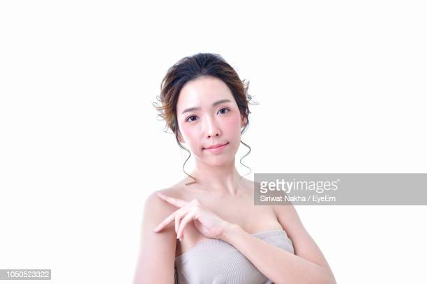 portrait of young woman against white background - ストラップレス ストックフォトと画像