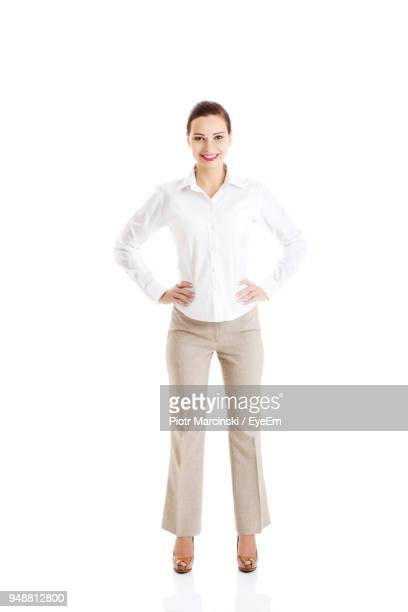 portrait of young woman against white background - handen op de heupen stockfoto's en -beelden