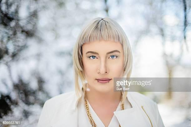 portrait of young woman against winter landscape - bob frisur stock-fotos und bilder