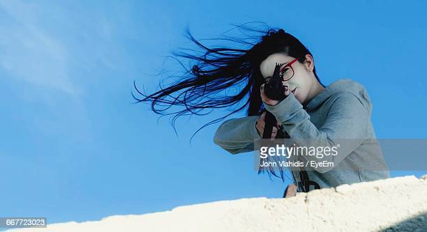 portrait of young woman aiming with airsoft gun against sky - air soft gun foto e immagini stock