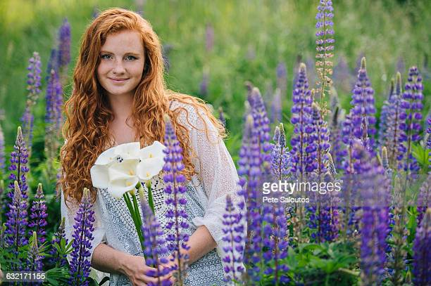 Portrait of young woman amongst purple wildflowers holding bunch of lilies