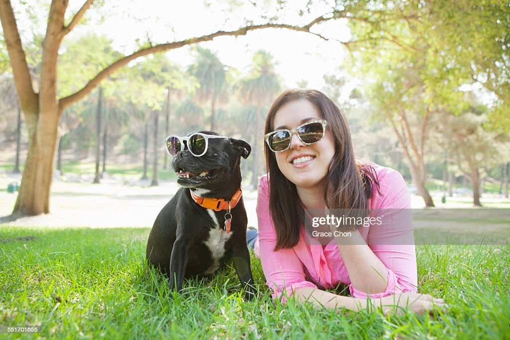 Portrait of young woman and dog lying in park wearing sunglasses : Stock Photo