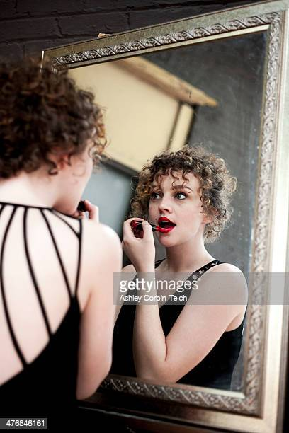Portrait of young woman applying lipstick in mirror