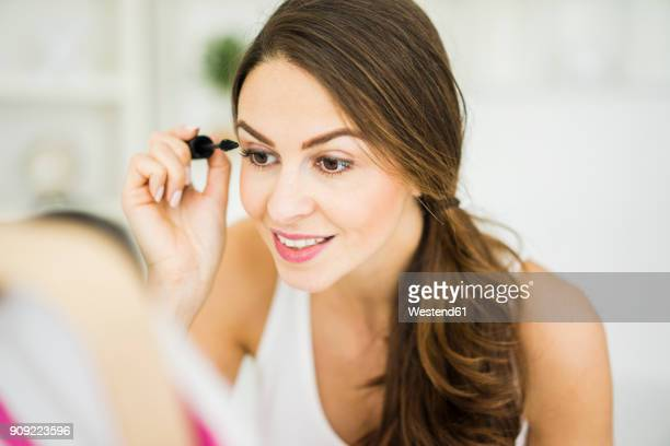 portrait of young woman applying mascara - eye make up stock photos and pictures