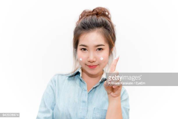 Portrait Of Young Woman Applying Moisturizer Against White Background