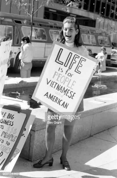 Portrait of young woman as she holds a sign that reads 'Life is for people Vietnamese and American' outside the Time Life Building during the...