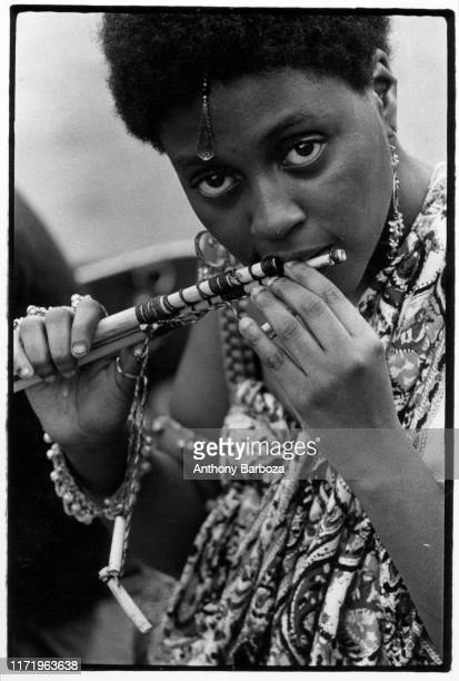 Portrait of young woman as she plays a bamboo flute in Washington Square Park New York New York 1960s