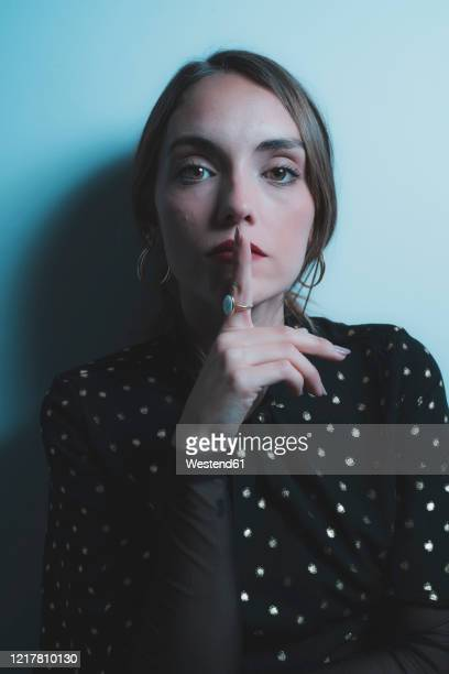 portrait of young woman asking for silence - request stock pictures, royalty-free photos & images