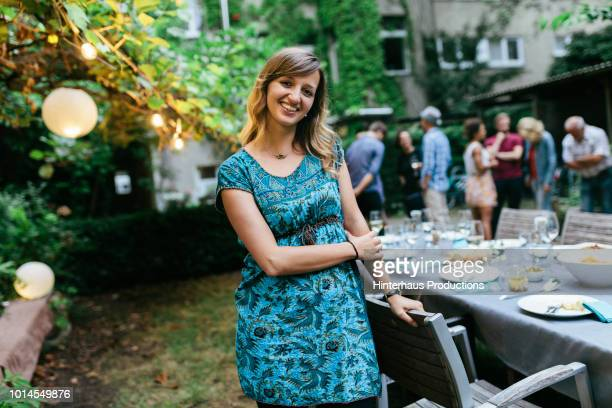 portrait of young woman at bbq with family - personne secondaire photos et images de collection