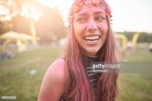 Portrait of young woman at festival, covered in colourful powder paint