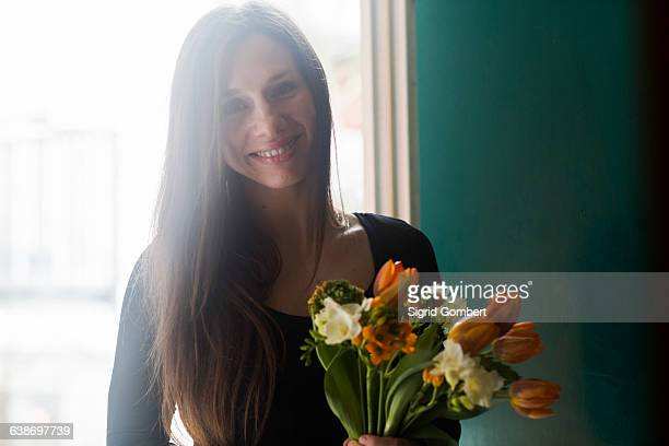portrait of young woman at home, holding flowers, smiling - sigrid gombert stock-fotos und bilder