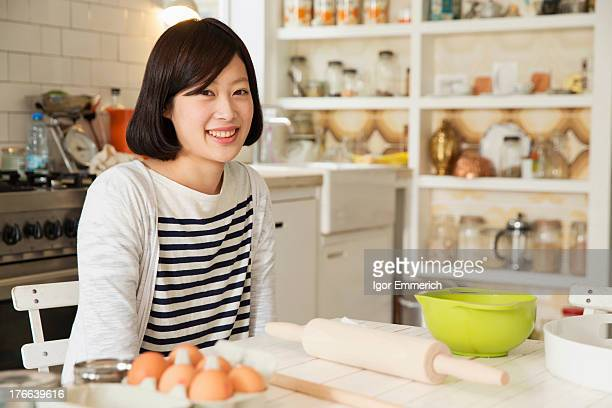 Portrait of young woman at kitchen table with baking ingredients