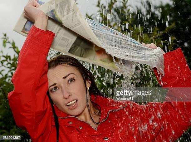 Portrait of young woman at rainfall holding newspaper over her head