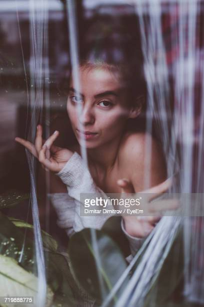 Portrait Of Young Woman Behind Curtain