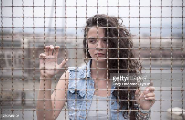 Portrait Of Young Woman Behind Fence