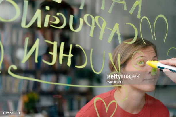 portrait of young woman behind windowpane in a cafe with hand writing - ver através - fotografias e filmes do acervo