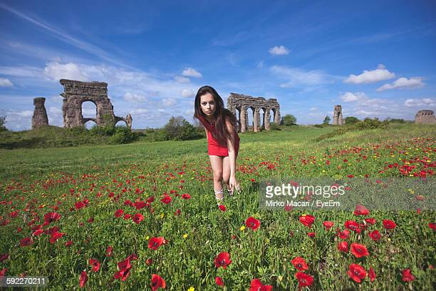Portrait Of Young Woman Bending On Flowering Field Against Sky