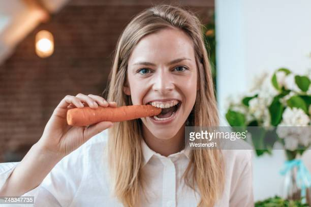 Portrait of young woman biting carrot