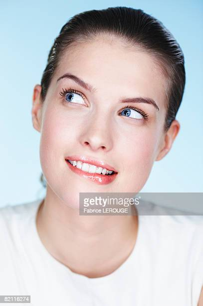 Portrait of young woman biting lips and looking up
