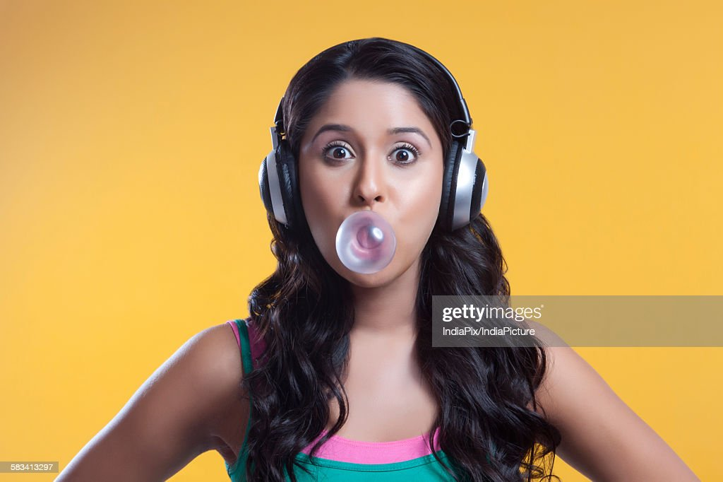 Portrait of young woman blowing a bubble : Stock Photo