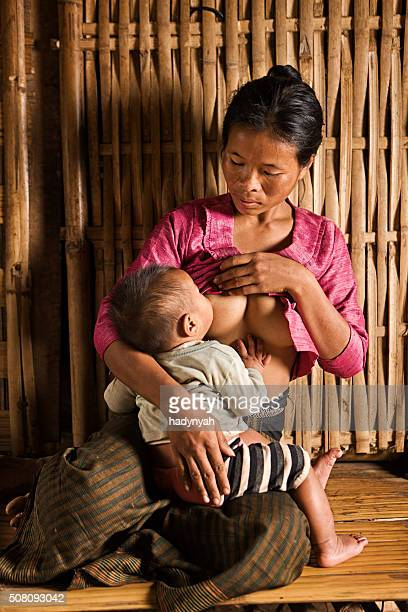portrait of young woman breastfeeding her baby in northern laos - adult breastfeeding photos stock pictures, royalty-free photos & images