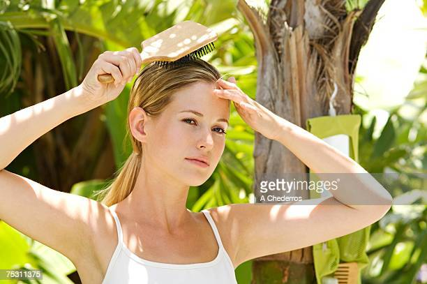 Portrait of young woman brushing her hair, outdoors