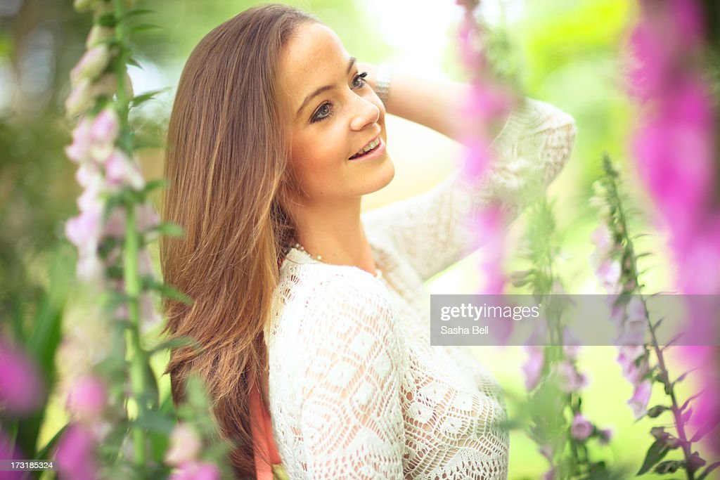 Portrait of young woman by foxgloves : Stock Photo