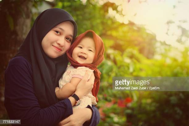 portrait of young woman carrying happy daughter against trees - traditional clothing stock pictures, royalty-free photos & images