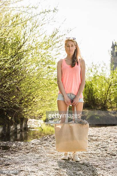 Portrait of young woman carrying shopping bag in park