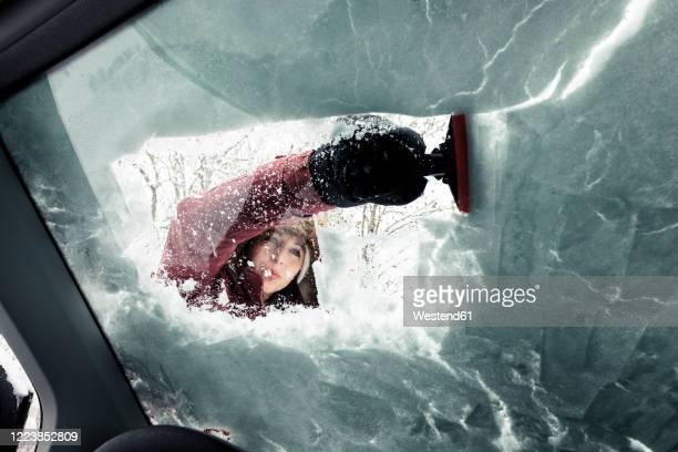 portrait of young woman cleaning snow from car's windscreen - bevroren stockfoto's en -beelden