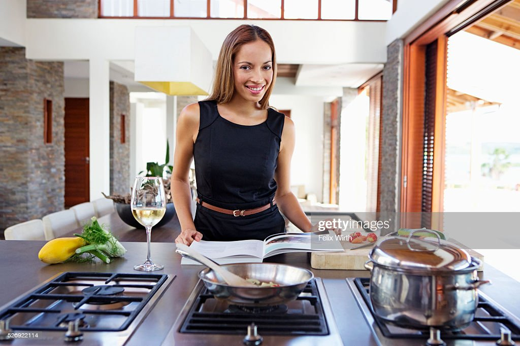 Portrait of young woman cooking dinner : Stock Photo